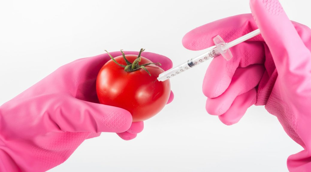 pink gloves holding a syringe in a tomato